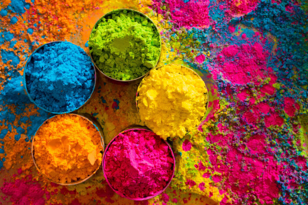 Holi festival-coloured powders spilled across a table with bowls filled with green, yellow, orange, pink and blue powders.