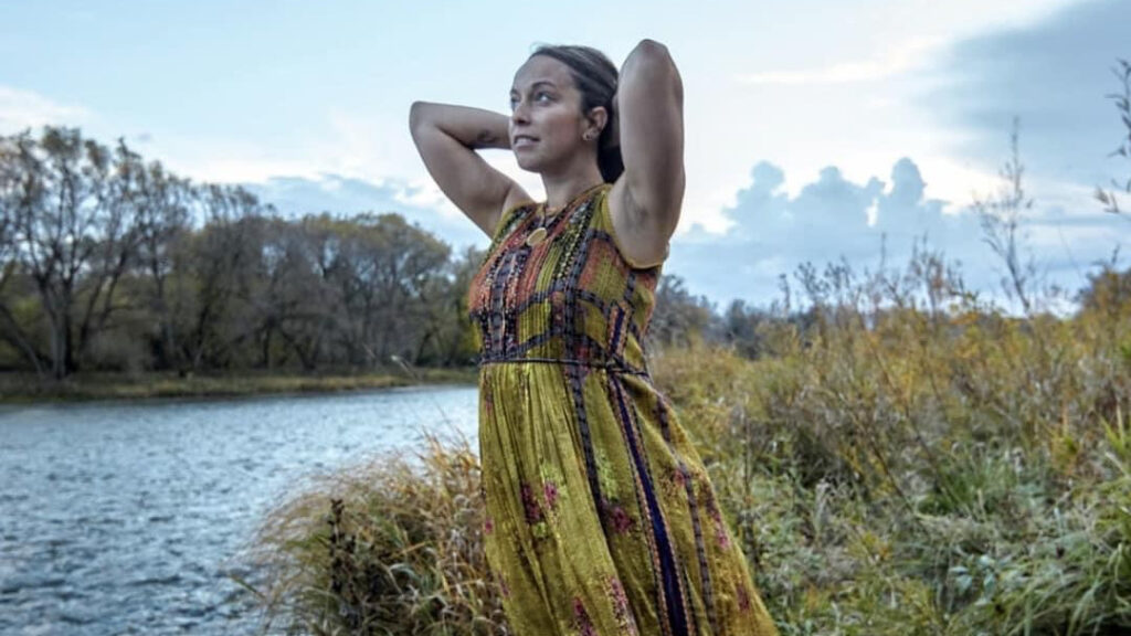 Evi Spiliotopoulos in an olive dress displaying wholehearted living while standing on the side of a river staring up at a cloud filled sky